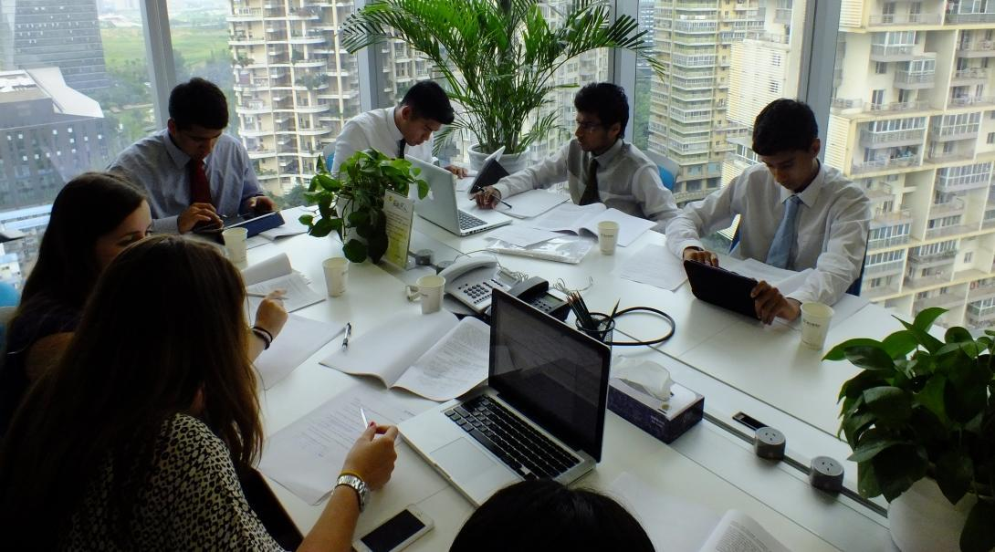 Business Interns sit around a table in a business meeting with proffessionals in China.